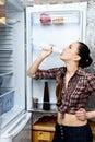 女孩在一个开放冰箱附近喝酸奶 库存图片