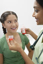 女性 生giving medicine to girl 免版税库存照片