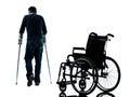 有拐杖的受伤的人 易地胜过轮椅silhou的 库存照片