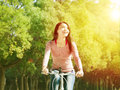相当亚 少妇骑马自行车在公园 图库摄影