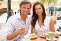 蛋糕享用年轻人的咖啡夫妇 免版税库存图片