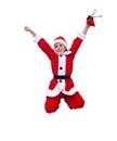 跳跃圣诞老人的服装的愉快的男孩 被隔  免版税库存图片