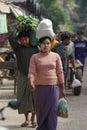 运载在 者的一名未认出的缅甸妇女米在市场在bagan,缅甸上 免版税库存照片