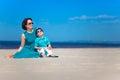 逗人喜爱的海滩热带她的小母亲的儿子 库存图片