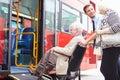 ônibus da placa de helping senior couple do motorista através da rampa da cadeira de rodas Imagem de Stock