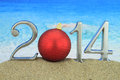 2014 with Christmas ball on the beach Royalty Free Stock Photos