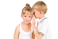 5-7 years old boy whispering to girl Royalty Free Stock Photos