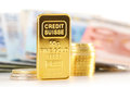 50 gram gold bar, banknotes and coins Royalty Free Stock Photo