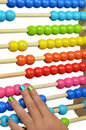 Abacus picture of a girls hand playing with a colourfull with isolated white background Stock Photos