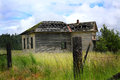 Abandonded school house side view of an old abandoned sits decaying in a grassy field under turbulent skies wire fence and posts Stock Photography