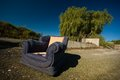 Abandoned armchair an dumped on waste ground polarizer filter used to enhance the sky Royalty Free Stock Photography