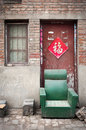 Abandoned armchair in a dusty hutong kaifeng china march an sits outside the door of typical home the city of henan province Royalty Free Stock Images