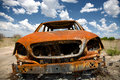 Abandoned car in field under blue sky a wide angle view of a rusty old puffy skies the game reserve of central kalahari botswana Stock Image