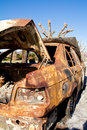 Abandoned car a rusty burned and in a mountain road Royalty Free Stock Image