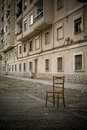 The abandoned chair in a poor street Stock Images