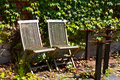 Abandoned chairs in the sun with erroded legs of tables Royalty Free Stock Image