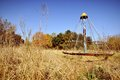 Abandoned children s playground an overgrown park with rusty equipment a roundabout or cone climber standing among tall grass in a Royalty Free Stock Image