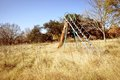 Abandoned children s playground an overgrown park with rusty equipment a slide standing among tall grass in a state of disrepair Royalty Free Stock Photo