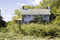 Abandoned colonial style house a is overgrown with weeds and shrubs looks to be Stock Image