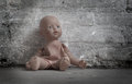 Abandoned doll sitting on a concrete floor Stock Image