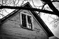 Abandoned farm house attic window of old with tree silhouette Stock Photo