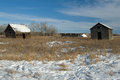 Abandoned farm in winter an with two sheds and a collapsed log barn a grassy field with snow image taken the morning Stock Photo