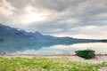 Abandoned fishing paddle boat on bank of Alps lake. Morning lake glowing by sunlight. Royalty Free Stock Photo
