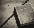 Abandoned holy bible bilbe over a rustic table close sitting in a wooden table Royalty Free Stock Image