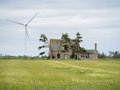 Abandoned home and windmill a hydro generating beside an abandonded worn old farm house Royalty Free Stock Photos