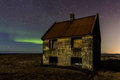 Abandoned house and some northern lights in the sky Stock Photo