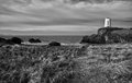 Abandoned lighthouse an on the small island of llanddwyn on the west coast of anglesey north wales the had it s five Stock Photo