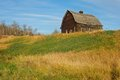 Abandoned log barn on top of hill an old a small slope with drying grass Royalty Free Stock Photography