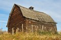 Abandoned log barn on top of hill an old a small slope with drying grass Royalty Free Stock Images