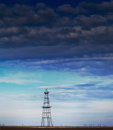 Abandoned oil rig profiled cloudy day sky active oilfield Stock Image