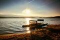 Abandoned old rusty pedal boat stuck on sand of beach wavy water level island on horizon autumn sunny at coastline weather Stock Photo