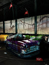 Abandoned park bumper cars in their place at the background we see a damaged and roller coaster useful image to illustrate Royalty Free Stock Photography