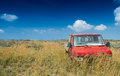 Abandoned red truck in the middle of a yellow meadow against blu Royalty Free Stock Photo