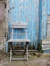 Abandoned rustic old wooden chair in farm yard blue grunge wooden old door Stock Images