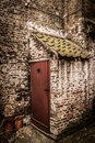 Abandoned toilet dark ancient outhouse with red door with heart window attached to a brick wall Royalty Free Stock Photography