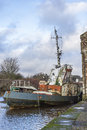 Abandoned tug magnus old rotting wooden fishing vessel tied up backwater chanel river annan annan harbour Stock Photo