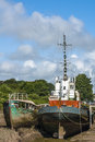 Abandoned tug magnus old rotting wooden fishing vessel tied up backwater chanel river annan annan harbour Stock Image