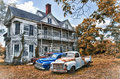 Abandoned Two Story Farmhouse with Three Vintage Automobiles Royalty Free Stock Photo