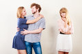 Abandoned woman with enamored couple jealousy and betrayal concept unloved girl watching on happy hugging triangle relationship Stock Photography