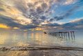 Abandoned wooden jetty at dusk old and damaged with romantic colorful cloudscape on the coastline of sulawesi indonesia sense of Royalty Free Stock Photo