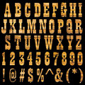 Abc wood textured containing letters numbers signs and symbols isolated on black background Royalty Free Stock Photos