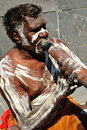 Aboriginal man with didgeridoo australian busker playing in central city Royalty Free Stock Image