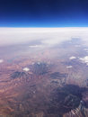 Above the andes of peru ariel view over mobile deep blue sky clay colored mountains scattered clouds flying in plane Stock Photo