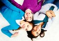 Above angle of attractive friends looking at camera while lying on the floor Royalty Free Stock Photos