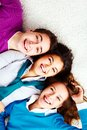Above angle of three laughing friends looking at camera Royalty Free Stock Photo
