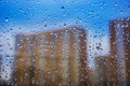 Abstract background. Drops of water on the window. High-rise buildings. Royalty Free Stock Photo